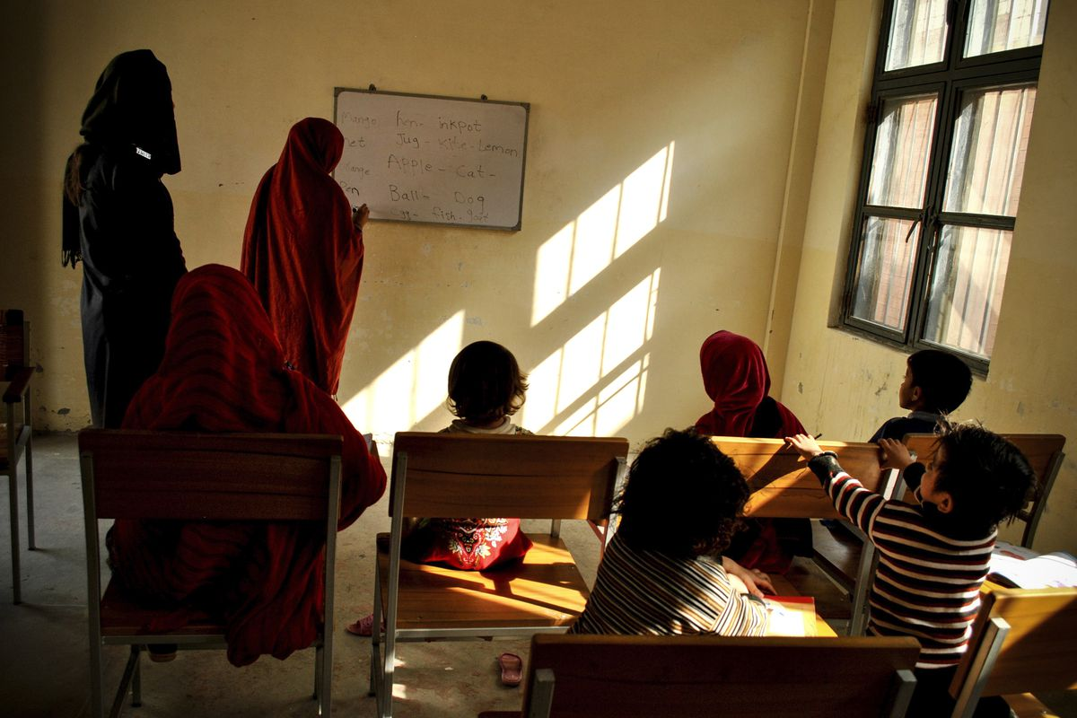 November 8: A prisoner teaches fellow inmates and their children at a central jail in Mardan, Pakistan. The local education department has launched a literacy program to increase employment opportunities for them upon their release. Saba Rehman/AP)