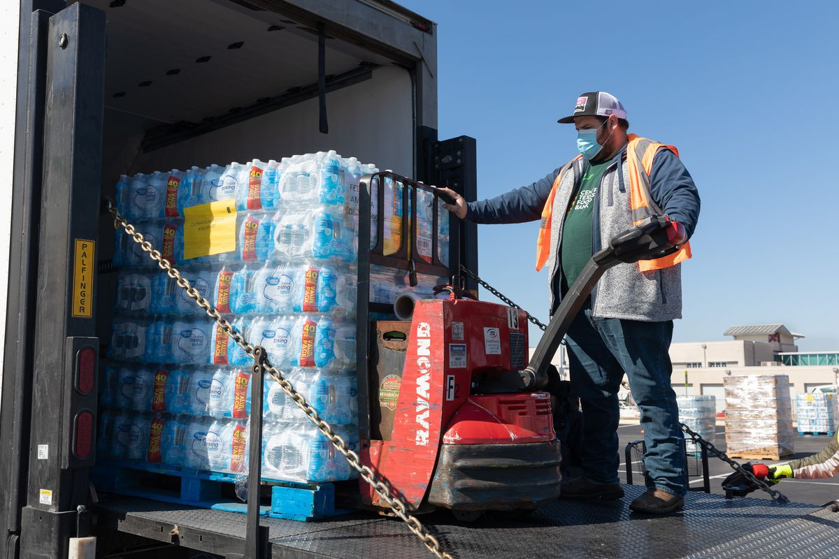 Volunteers load bottle water packs as part of Central Texas Food Bank's distribution over the weekend in Del Valle