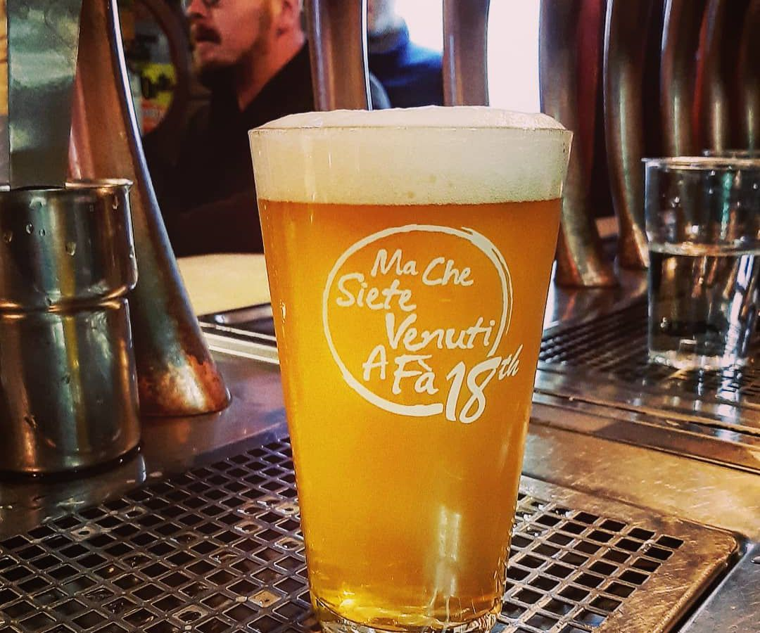 A branded pint glass full of beer on a bar