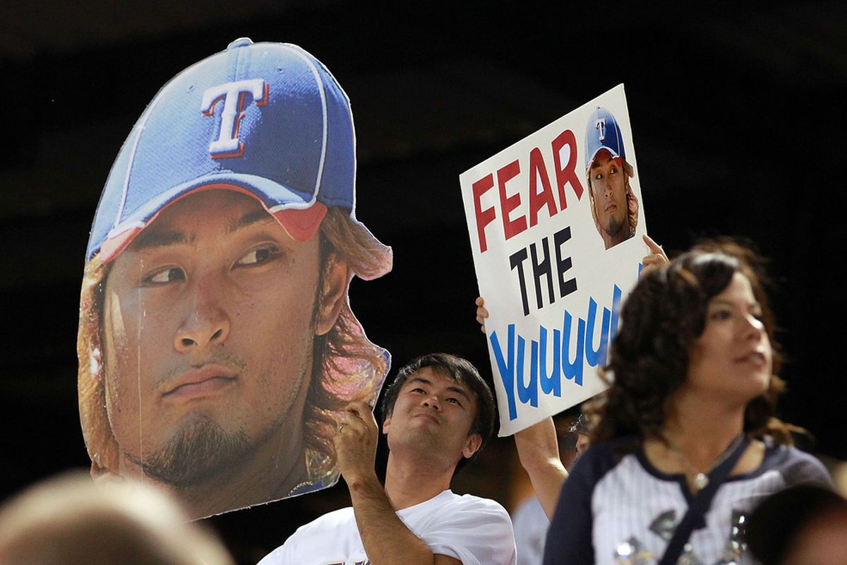 ARLINGTON, TX - APRIL 24:  Fans hold up signs for Yu Darvish #11 of the Texas Rangers during play against the New York Yankees at Rangers Ballpark in Arlington on April 24, 2012 in Arlington, Texas.  (Photo by Ronald Martinez/Getty Images)