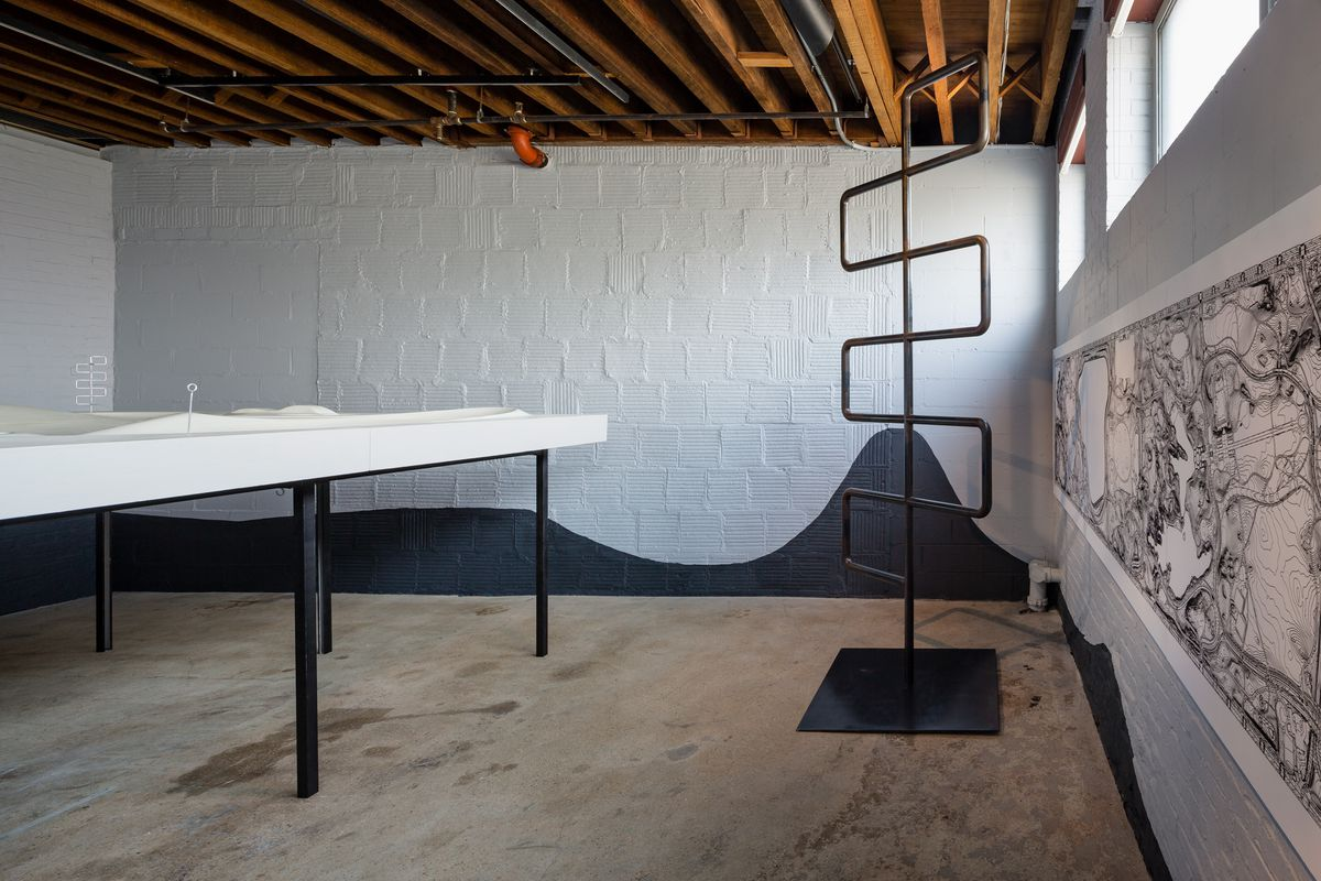 An installation of the white plaster cast of Contoured Playground set on a 5-foot-tall table and an eight-foot-tall metal climbing structure in a gallery with brick walls and a wood-beam roof