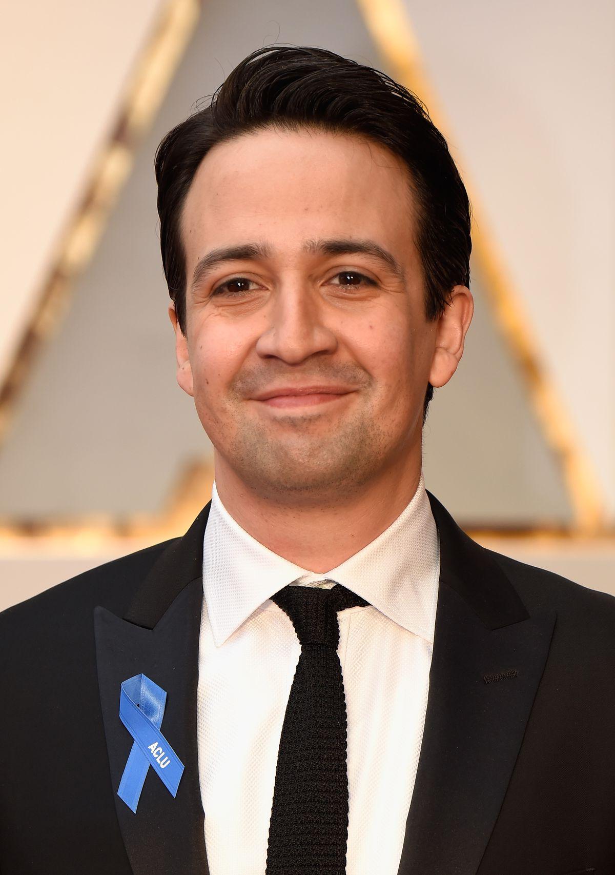 Lin Manuel-Miranda with ACLUE blue ribbon on Oscars red carpet