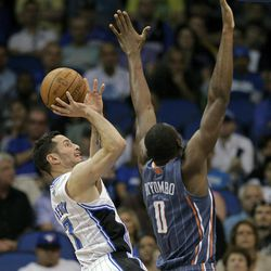Orlando Magic's J.J. Redick, left, takes a shot over Charlotte Bobcats' Bismack Biyombo (0) during the first half of an NBA basketball game, Wednesday, April 25, 2012, in Orlando, Fla.