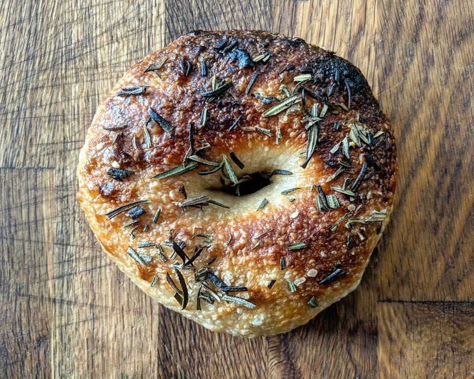 A charred bagel with a bubbly crust is topped with rosemary and salt and sits on a wooden counter