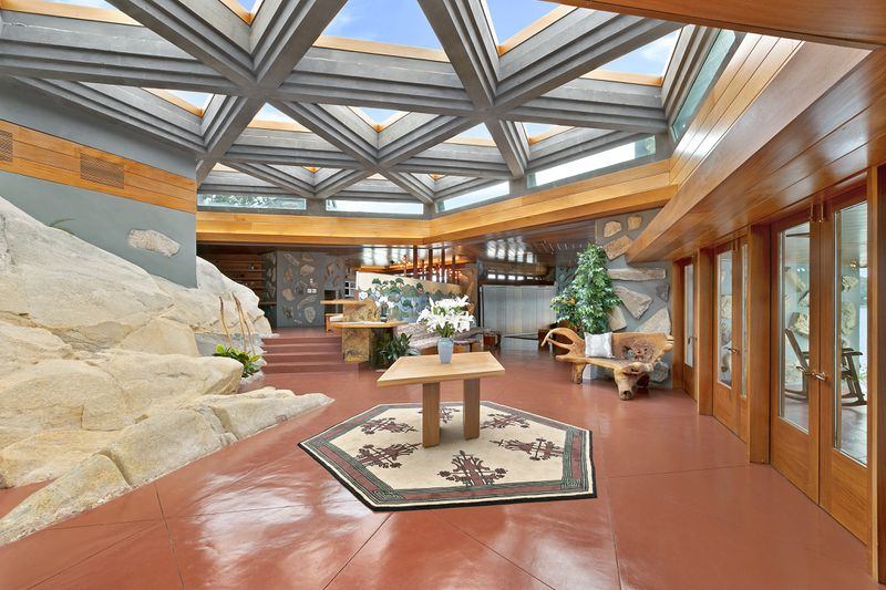 A living area with a ceiling that has partitioned skylights and a red glossy floor. One of the walls has a section that is decorated with rock. There is a table that has a blue vase with white flowers.