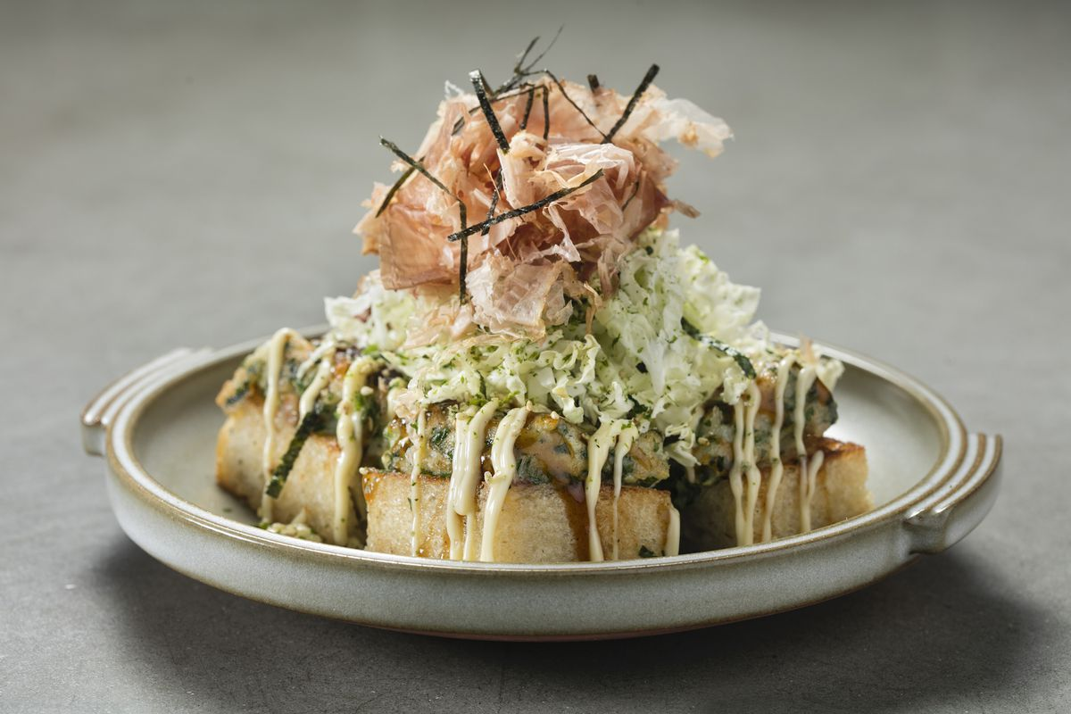 A Japanese layered pancake placed on a white plate includes a yellow base, shredded cabbage on top, and dried fish on top of that