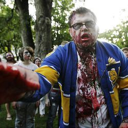 Dale Fink plays the part of a zombie in the third annual Zombie Walk in downtown Salt Lake City Sunday. Participants made their way around downtown in a somewhat orderly fashion, with many limping along the way.