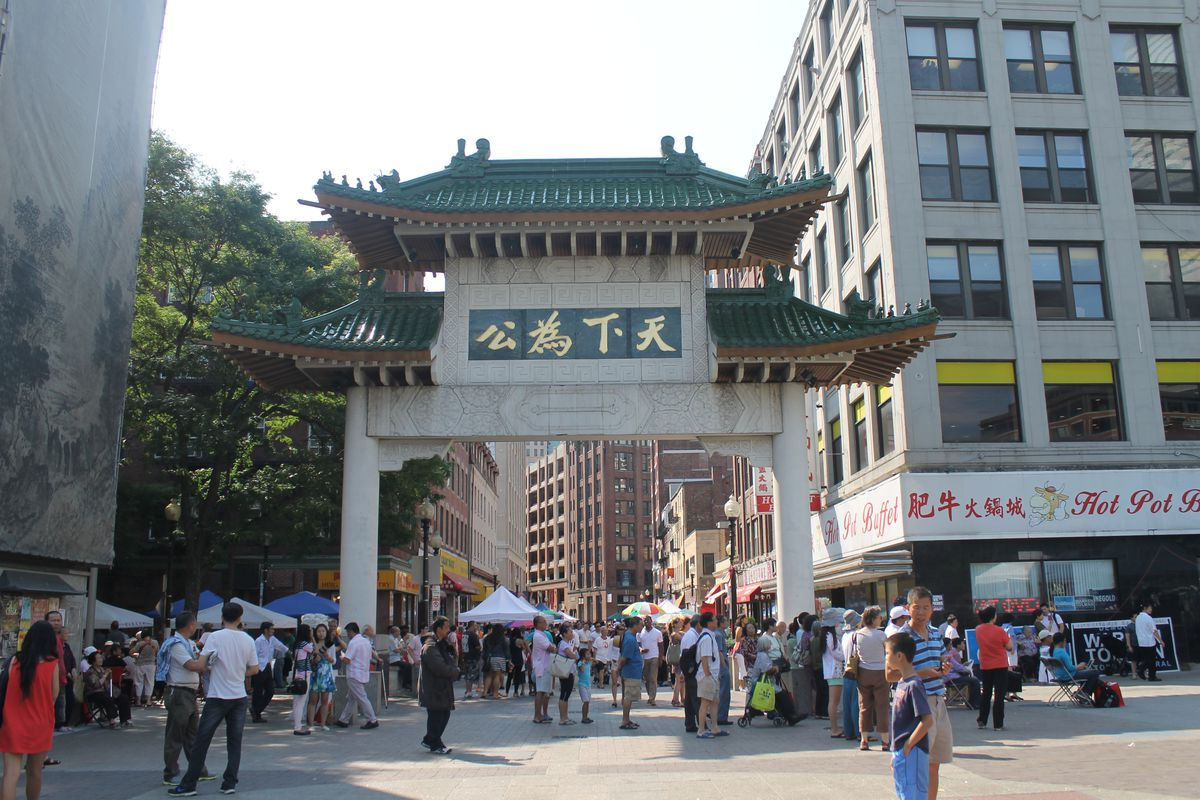 A large, ornamental gate on a busy street.