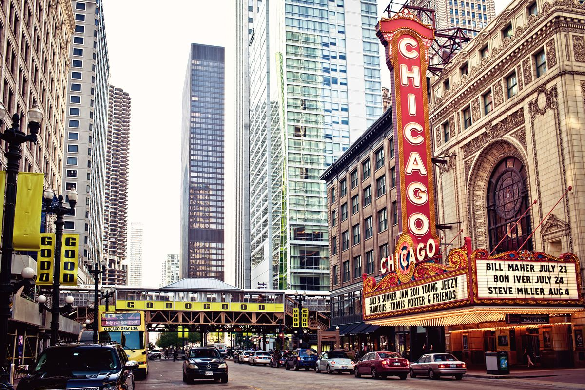 A city street lined with tall buildings and a large theater marquee.