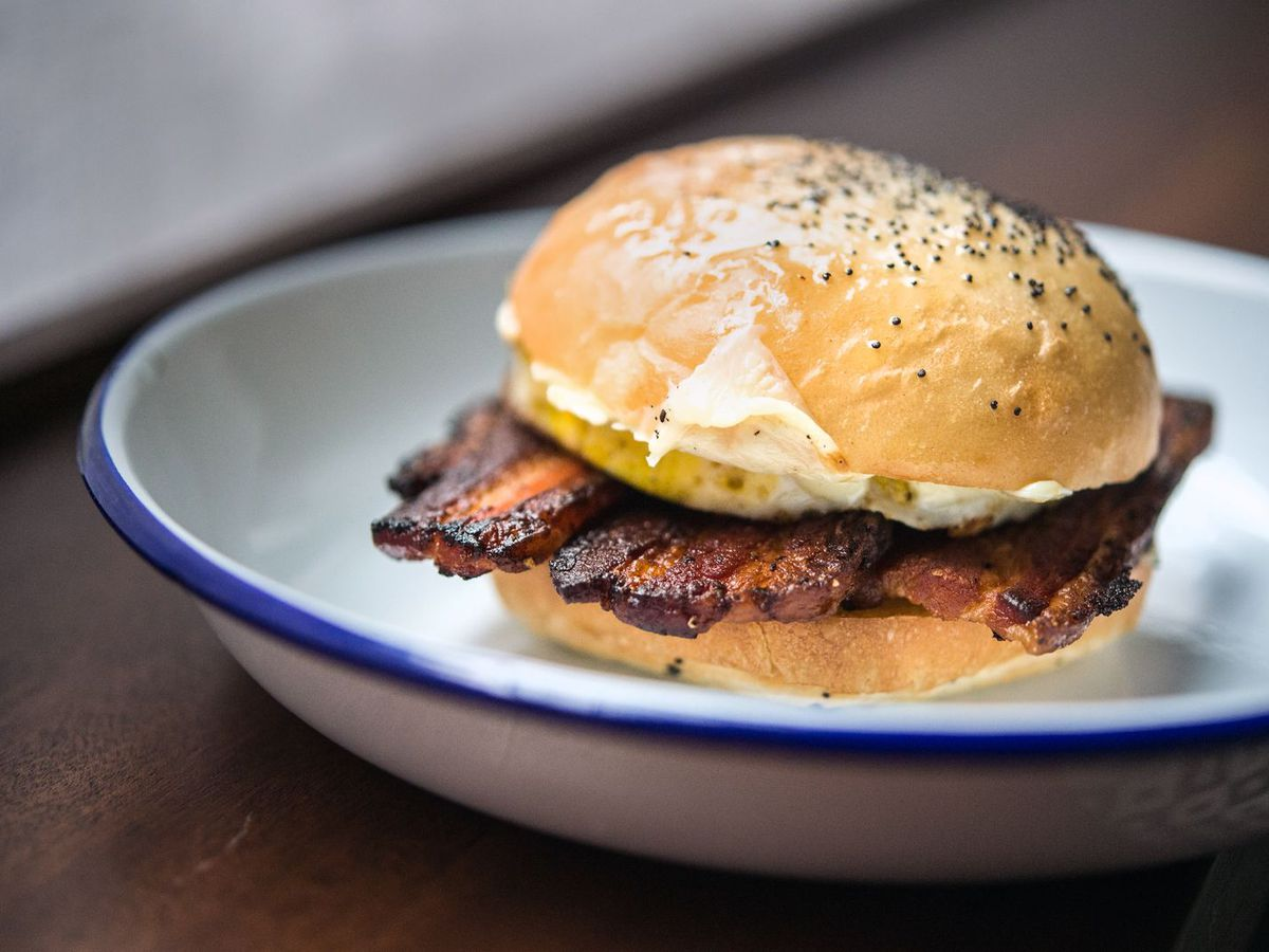 A breakfast sandwich with thick-cut bacon and a poppy seed roll on a blue-rimmed white plate