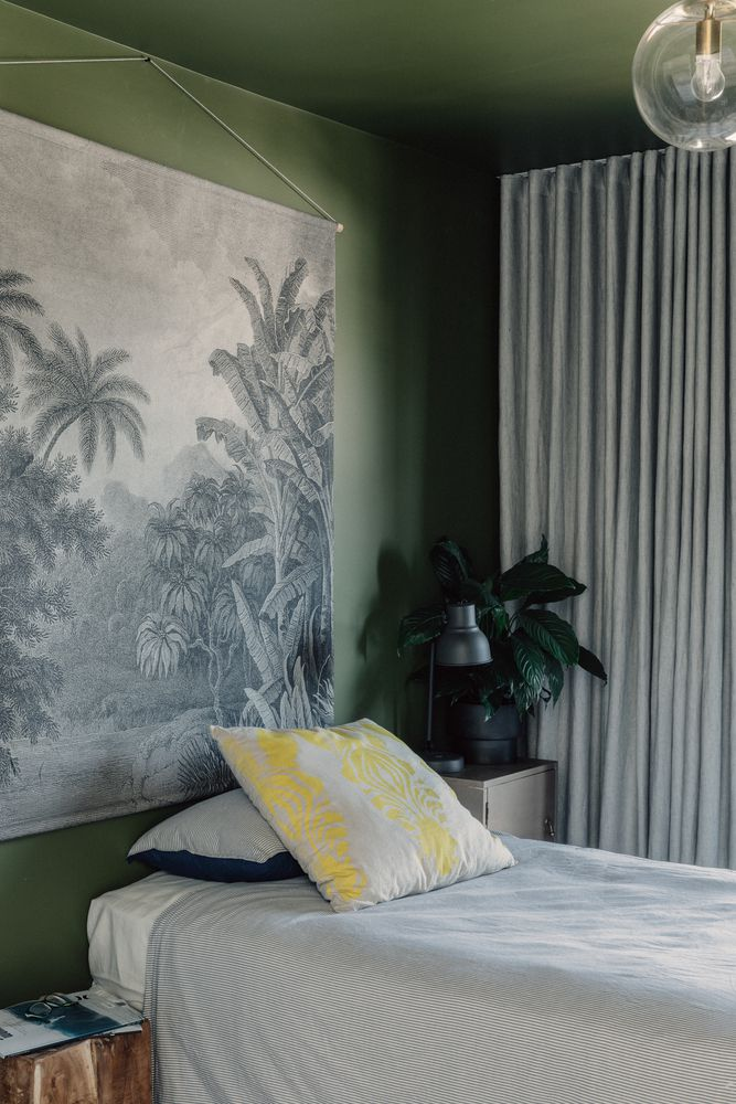 Bedroom with olive green walls, a desktop plant, and light gray curtains.