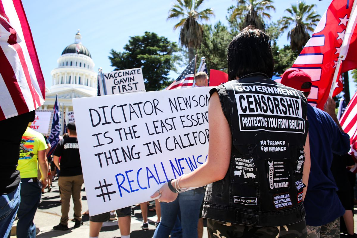 """A protester holds a placard that says """"Dictator Newsom Is the Least Essential Thing In California #RecallNewsom."""""""