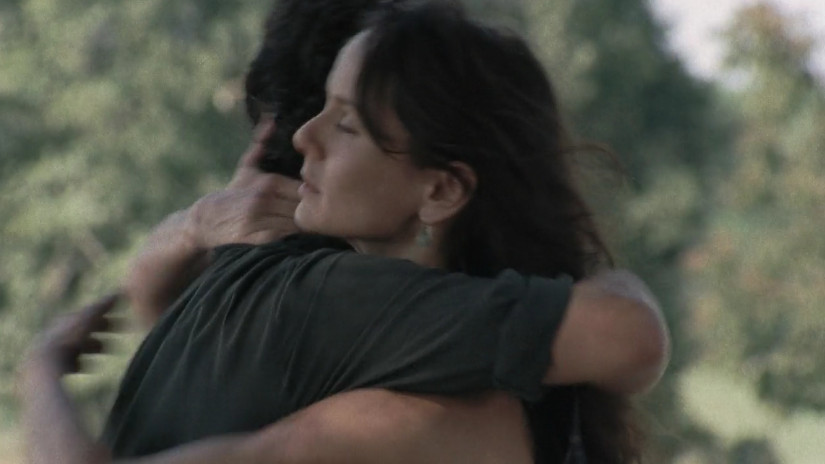 A man and a woman hug. There are trees in the background.