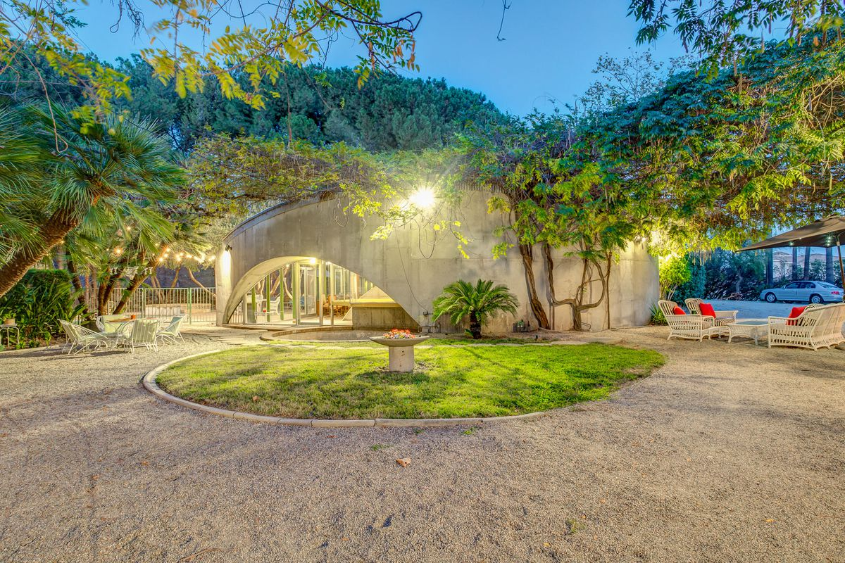 Exterior shot from courtyard of curved concrete facade and arched window.