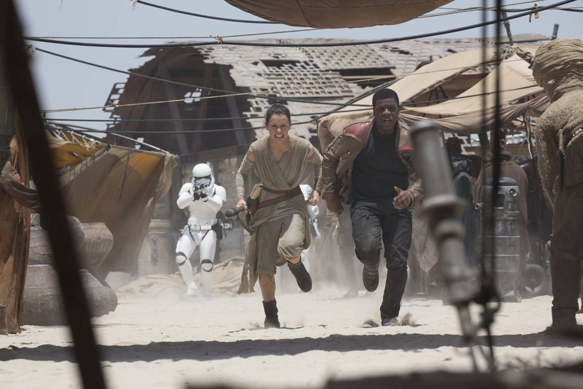 Rey and Finn flee from Stormtroopers in The Force Awakens.