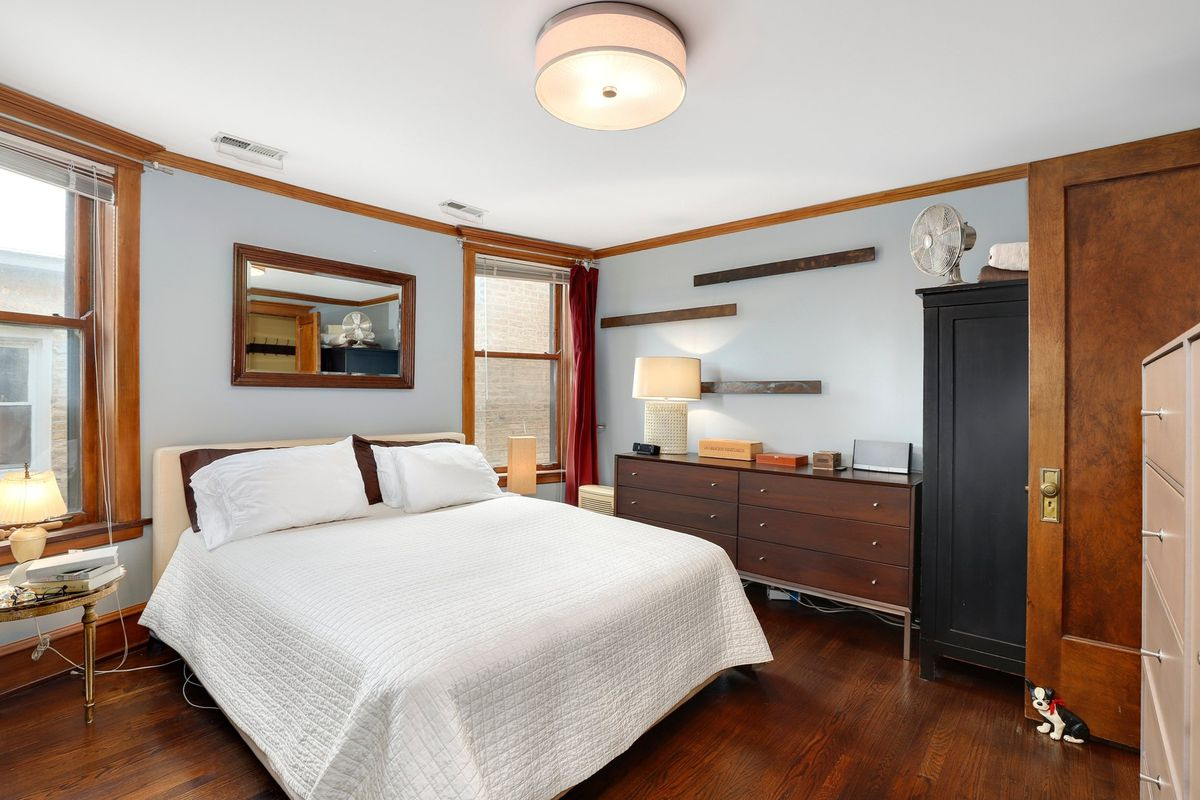 A bed sits between two windows in a room with hardwood floors and midcentury-inspired wood dressers.