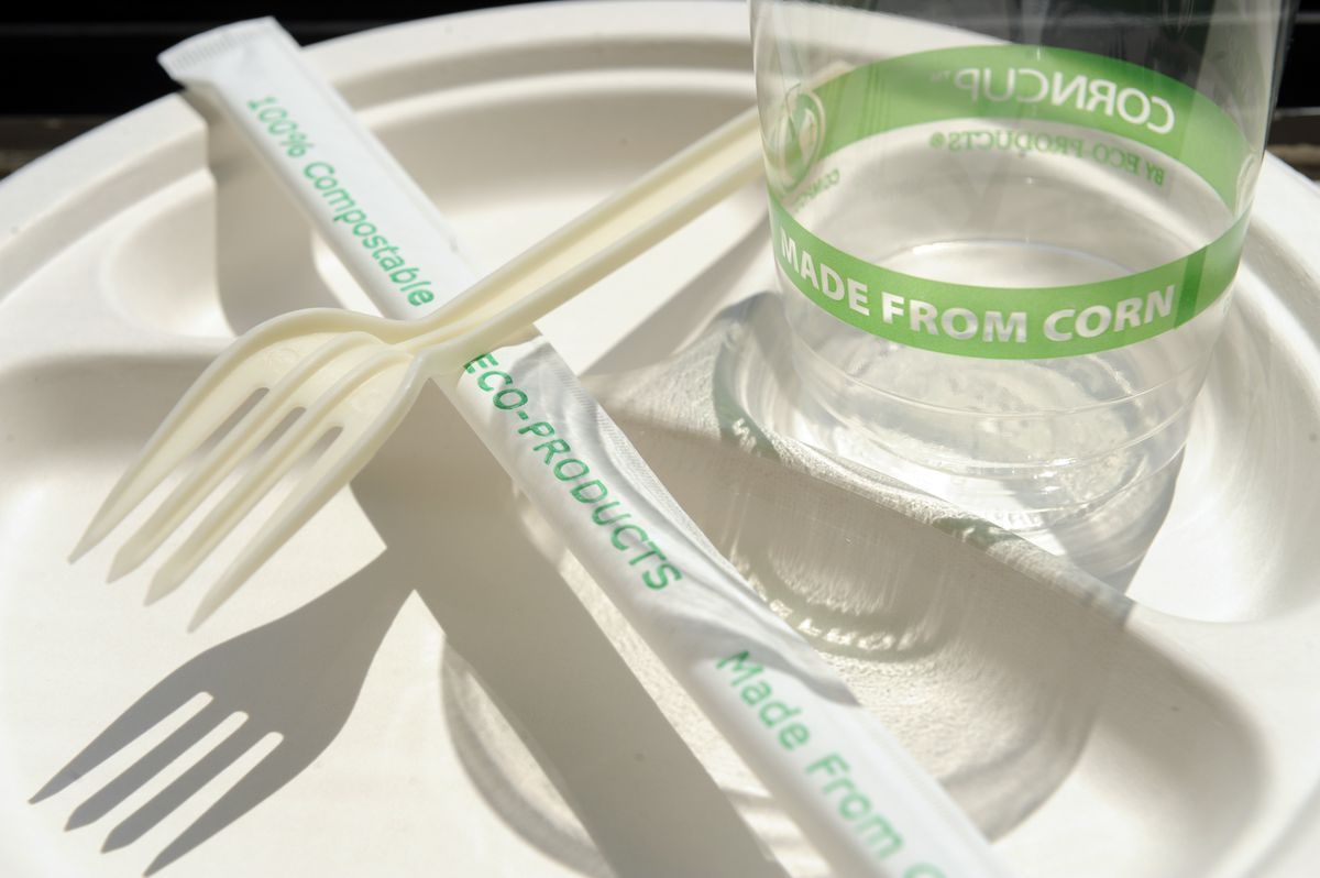A compostable cup, fork, and straw in its wrapper.