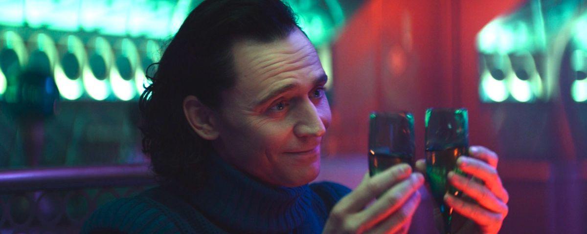 Loki lifting two flutes of champagne in bisexual lightning