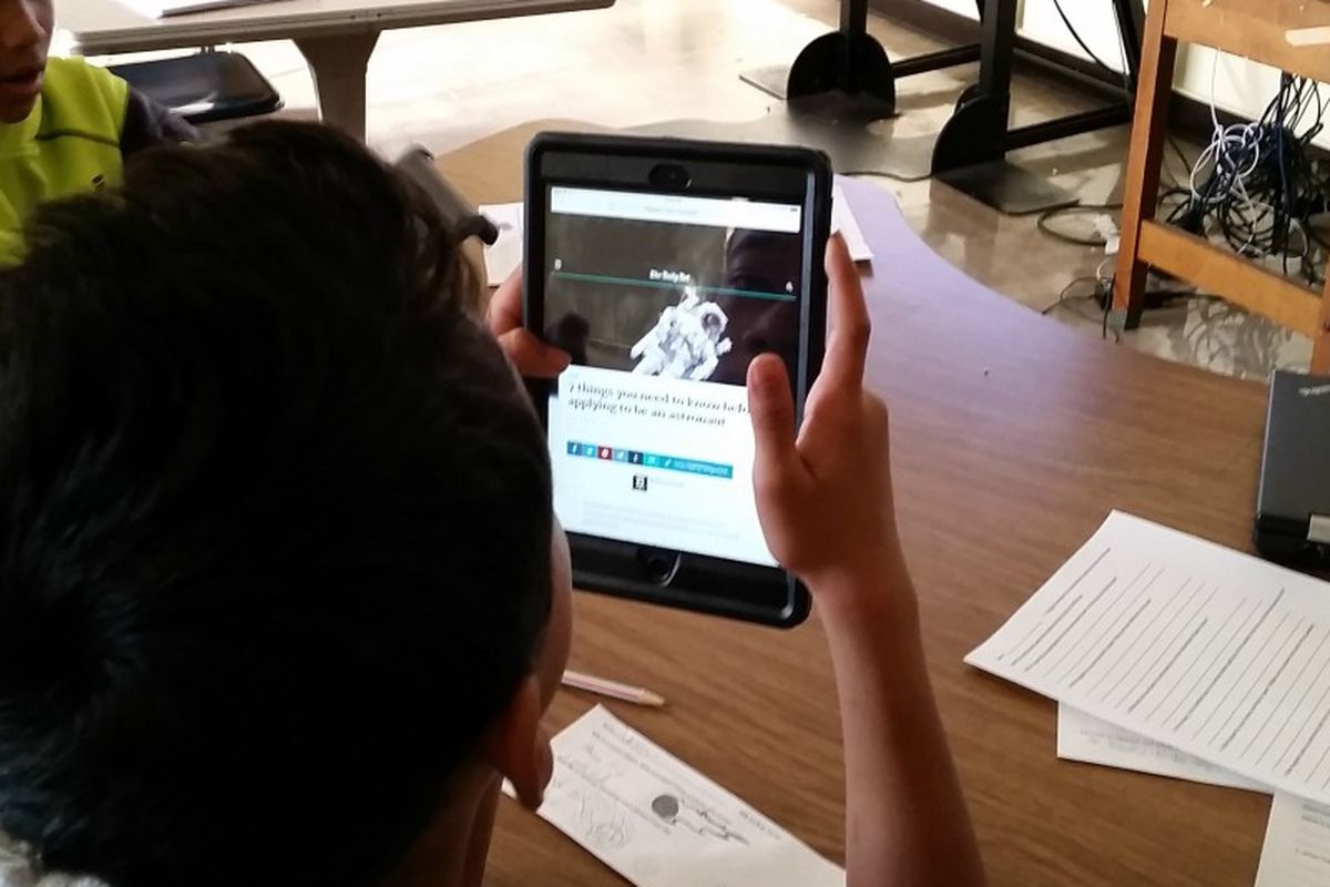 A student uses an iPad to learn about space