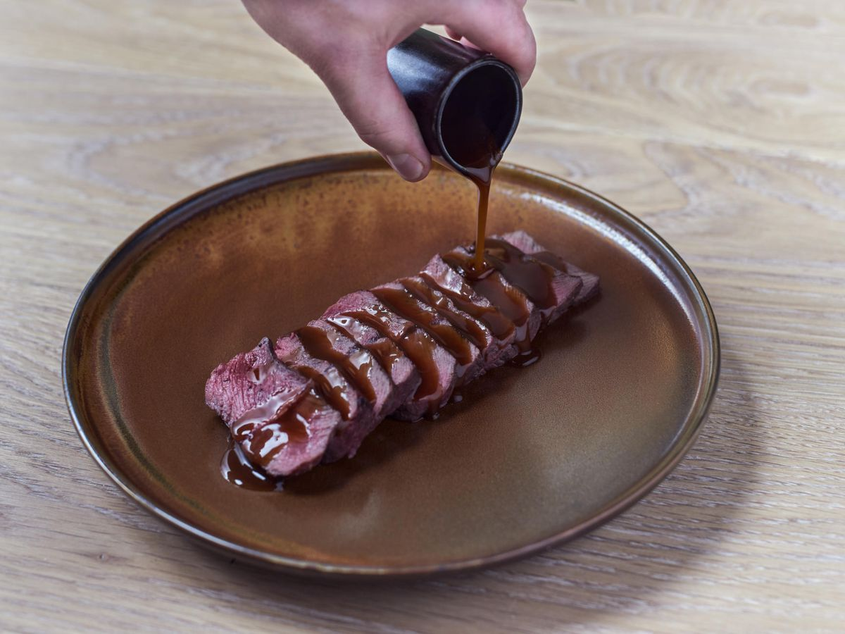 The hand of a server pours steak sauce over slices of beef arrayed on a decorative plate on a neutral wood background