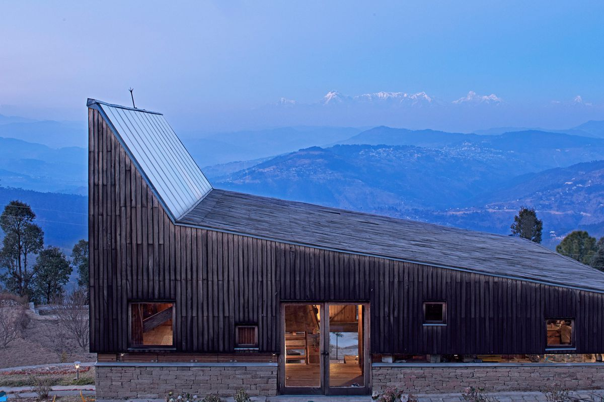 Wood-framed home with gently pitched sloping roof that peaks dramatically at one end in mountain setting.