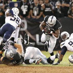 Oakland Raiders running back Darren McFadden (20) runs against San Diego Chargers linebacker Donald Butler (56) and defensive tackle Corey Liuget (94) during the first quarter of an NFL football game in Oakland, Calif., Monday, Sept. 10, 2012.