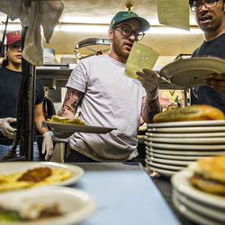 Jackie Ruvalcaba [left], Wes Moore [center], and Kamen Miller make sure that orders are correct before they leave the kitchen at  Home Grown.
