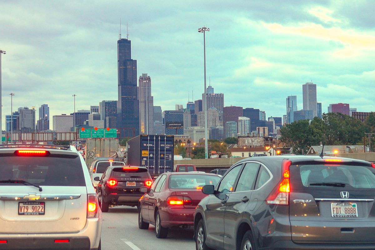Cars on an expressway with red brake lights lit up head towards a city's downtown with tall towers in the distance collected together against a cloudy sky.
