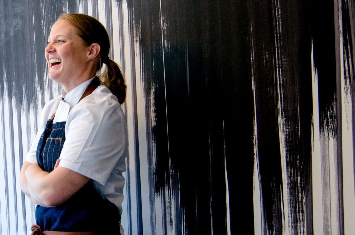 Chef Sarah Wade stands in front of a black-and-white-striped background, wearing a denim chef apron, looking off to the side, crossing her arms, and laughing.