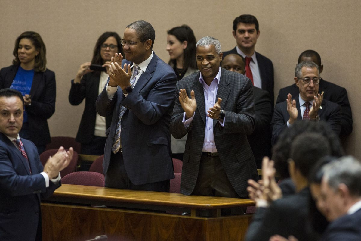 Obama Foundation civic engagement chief Michael Strautmanis (left) and Martin Nesbitt, chairman of the board of the Barack Obama Foundation, applaud after the Chicago City Council cast a unanimous vote Wednesday morning in favor of the Obama Presidential
