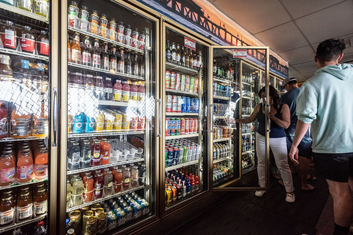A woman reaches into a grocery store fridge for a drink.