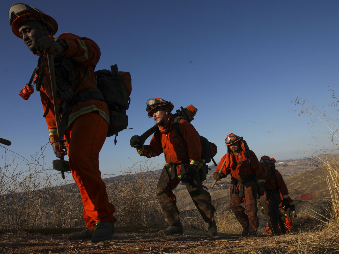 A line of men in orange fireproof jumpsuits, their faces blackened with soot, carry bulging rucksacks and tools through tall brown grass.