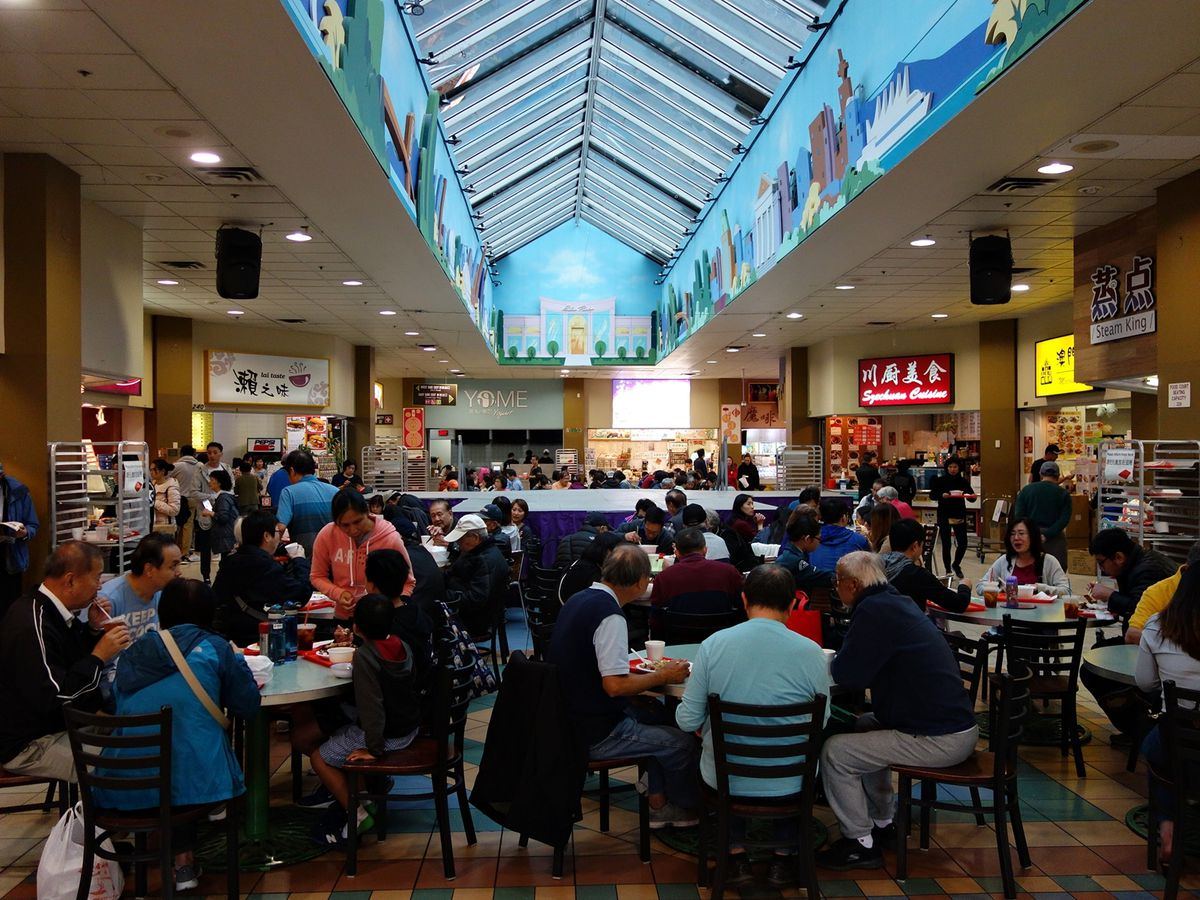 Crowds sit at tables in the center and wander around vendors set on the outer rim of a light-filled atrium with a large skylight
