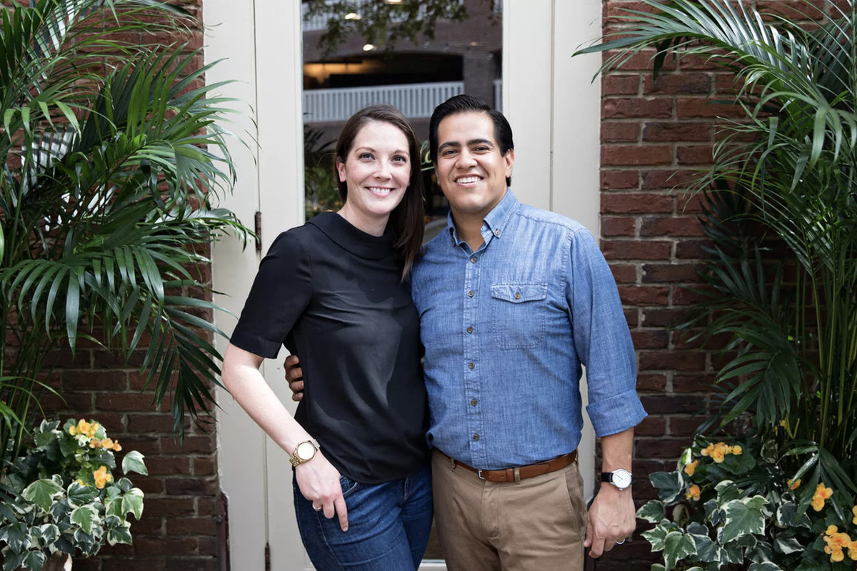 Caitlin Toscano, wearing a black shirt and jeans, and Michael Toscano, wearing a denim button-up and khakis, stand together with their arms around each other