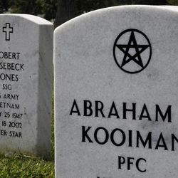 In this Aug. 20, 2010 photo, the tombstone for Pfc. Abraham Kooiman, a World War II veteran who died in 2002, is shown inscribed with a Wiccan religious symbol at Arlington National Cemetery in Arlington, Va.
