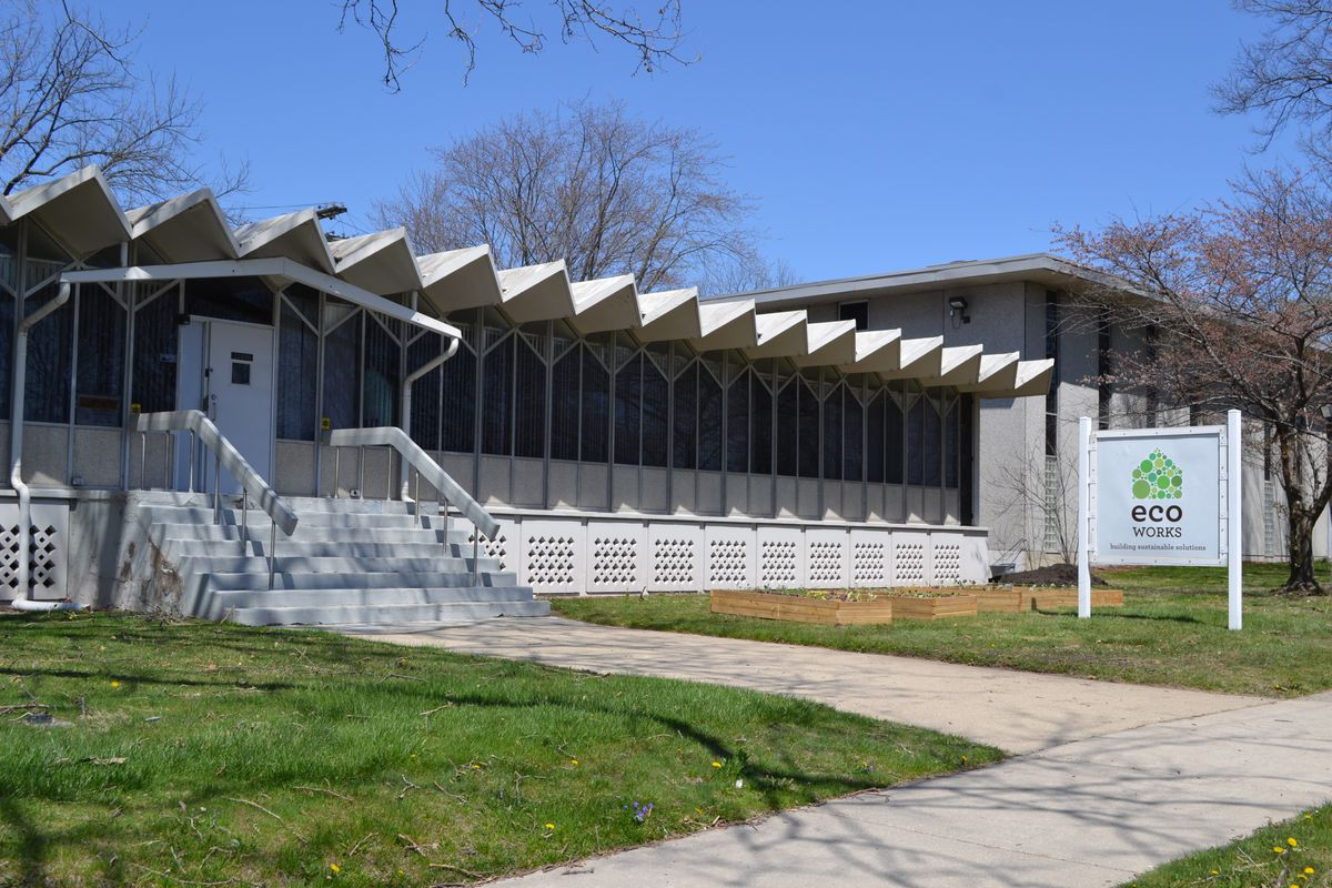 A long, one-story concrete building with a zigzag roof.