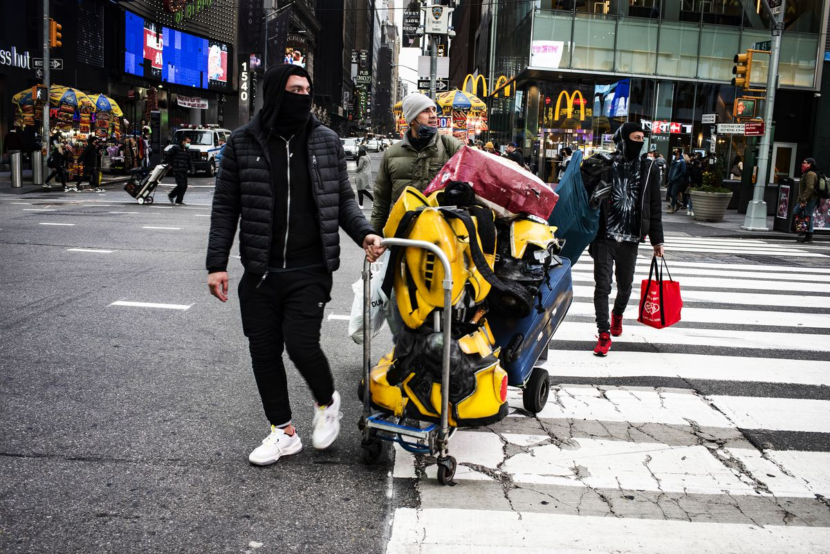 A group of men get ready for work as costumed characters during the holiday season. Times Square's unofficial tourism industry, including street performers and vendors, artists, souvenir shops, and ticket agents, has struggled but adapted to the new reality.