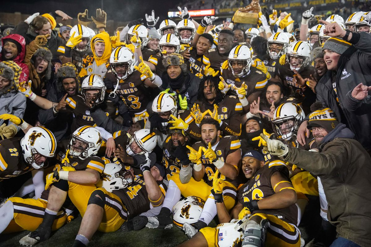 Wyoming Cowboys celebrate with the Bronze Boot trophy after win against the Colorado State Rams at Jonah Field War Memorial Stadium.