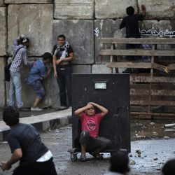 An injured Egyptian youth protester takes cover behind a metal barrier during clashes with riot police, unseen, behind cement blocks that are used to close the street leading to the U.S. embassy in Cairo, Egypt, Friday, Sept. 14, 2012, as part of widespread anger across the Muslim world about a film ridiculing Islam's Prophet Muhammad.