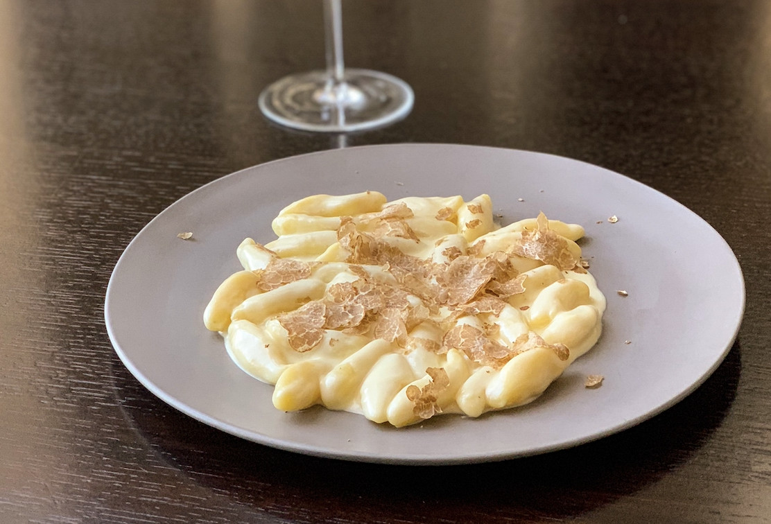 A white plate holding gnocchi topped with shaved black truffle.
