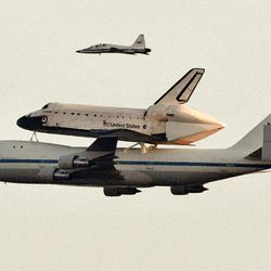 Space shuttle Endeavour sits atop the shuttle aircraft carrier, passes above the Austin, Texas, skyline Thursday, Sept. 20, 2012.   Endeavour is making a final trek across the country to the California Science Center in Los Angeles, where it will be permanently displayed.  (AP Photo/Statesman.com, Ralph Barrera)  MAGS OUT; NO SALES; INTERNET AND TV MUST CREDIT PHOTOGRAPHER AND STATESMAN.COM