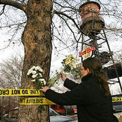 Jessica Kirby leaves flowers in the police tape at Trolley Square in Salt Lake City Tuesday morning.