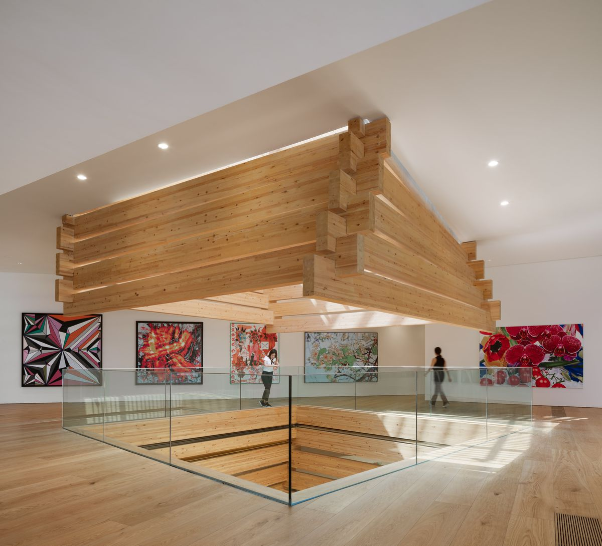 A gallery space with colorful square-shaped artwork on the walls surrounds a central atrium.