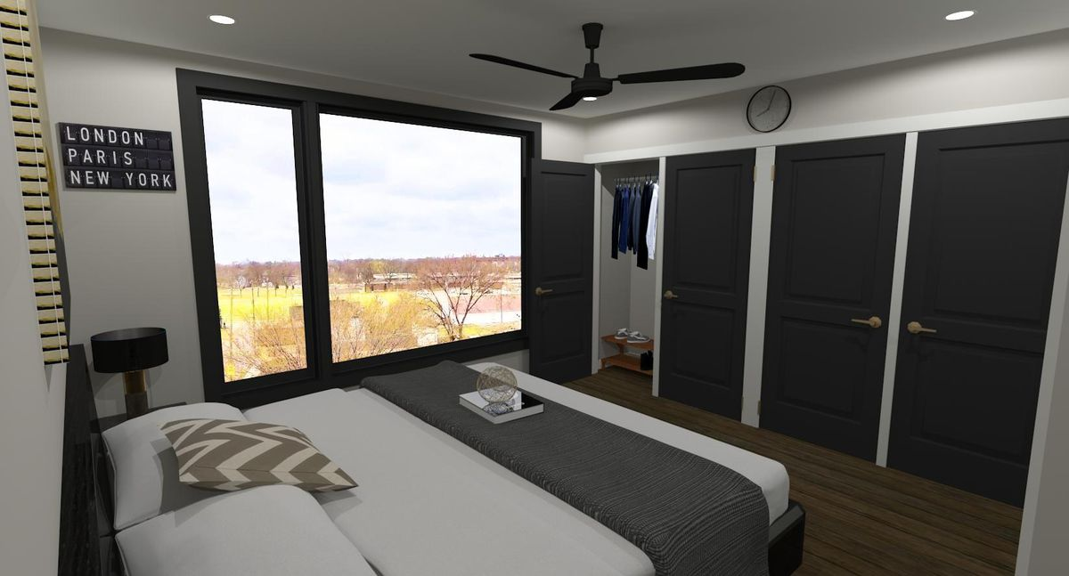 A wide bed faces closets with black doors and a window out to fall trees