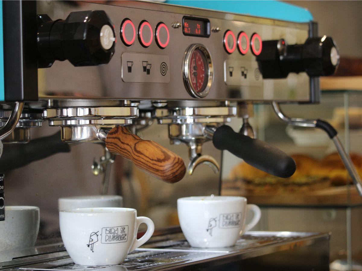 Two branded mugs sit beneath an espresso maker