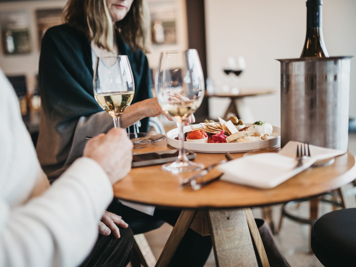 In a light-filled tasting room at Maryhill on the Vancouver Waterfront, where two people sit in front of two wine classes filled with white wine. A bottle sits in an ice bucket on the table.
