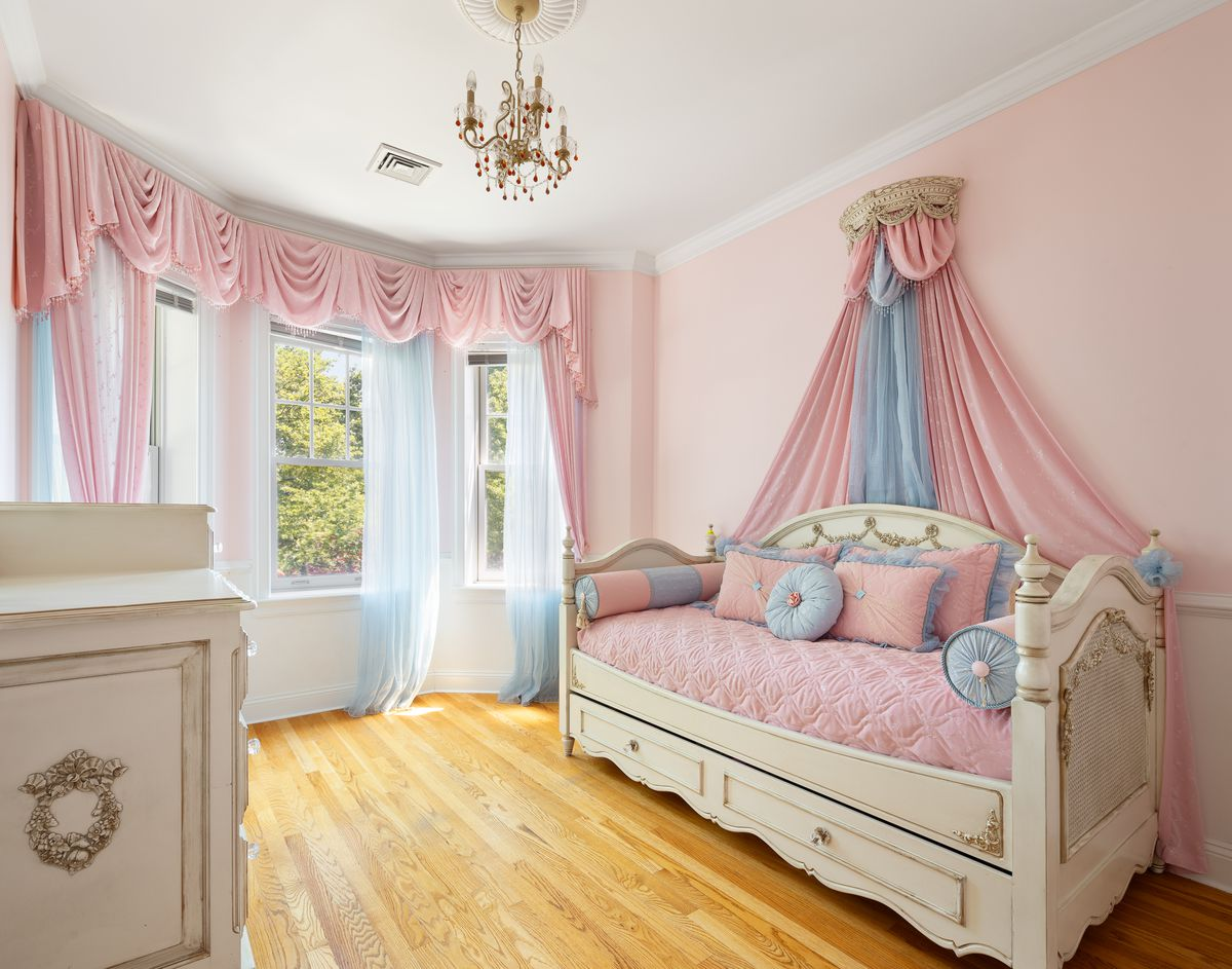 A bedroom with three windows, light pink walls, pink curtains, hardwood floors, a chandelier, and a couch.