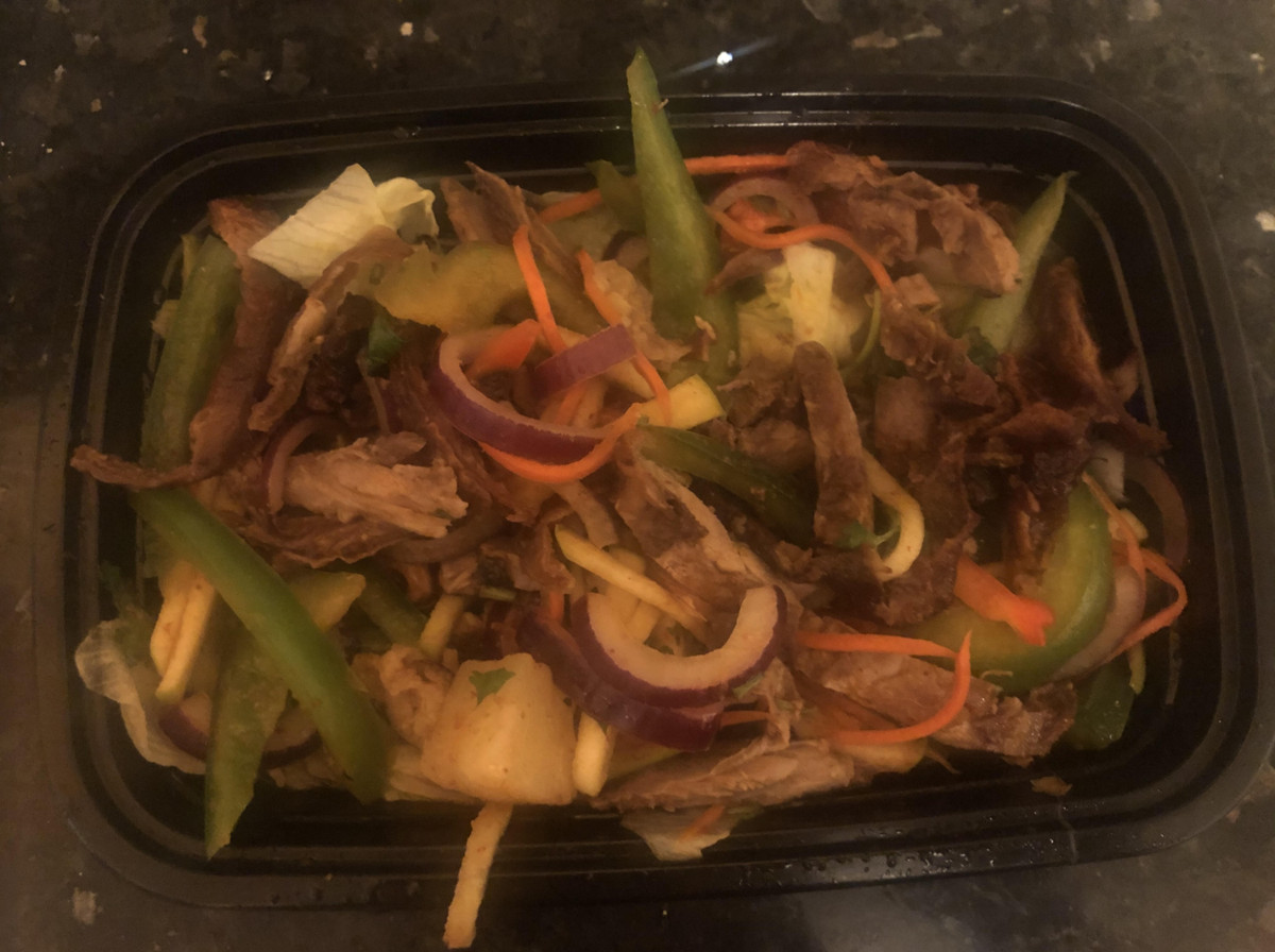 A black plastic container with shreds of food in it including vegetables, and pieces of meat