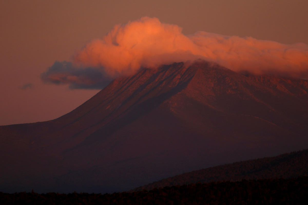 In this Monday, Aug. 7, 2017 photo, the first rays of sunlight color the clouds over Mount Katahdin in this view from the Katahdin Woods and Waters Scenic Byway outside Patten, Maine. Interior Secretary Ryan Zinke wants to retain the newly created Katahdi