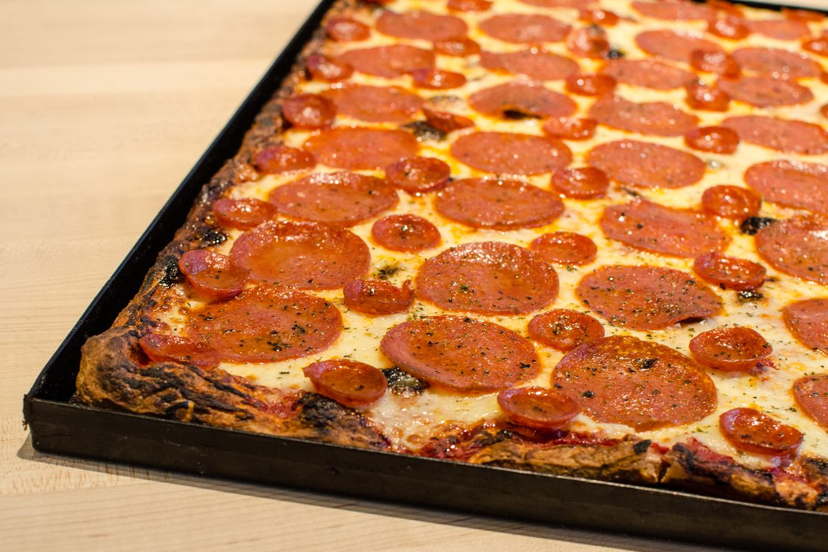 A pan of pepperoni pizza with an alternating pattern of big, flat pepperonis and small, curled pepperoni cups